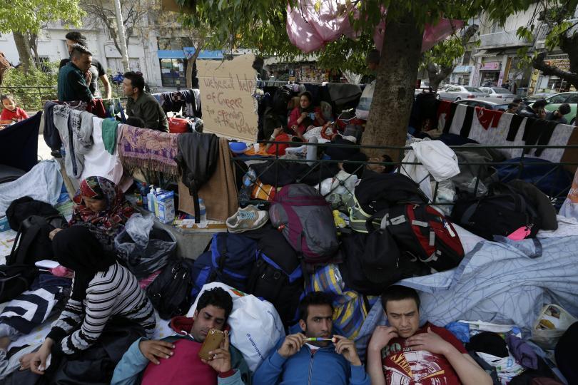 Мигранти почиват под дърво на площад Виктория в Атина