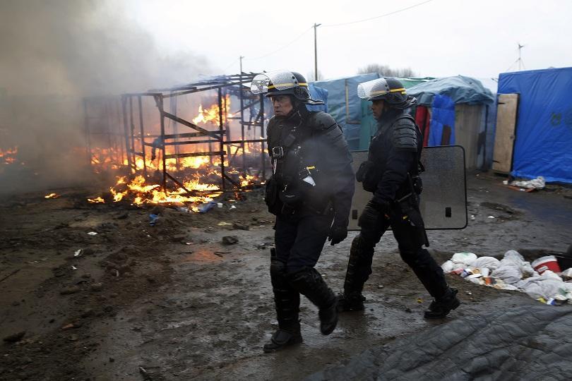 Полицаи вървят из импровизирания лагер в Кале, Франция