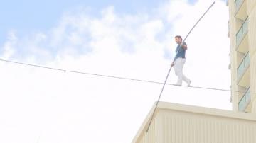 Акробат извървя разстоянието между два хотела върху тънко въже