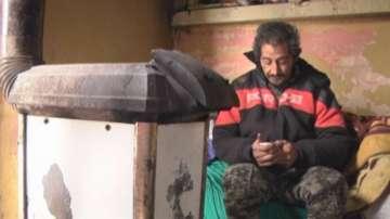 Бездомник получава дърва за огрев срещу почистване на сняг