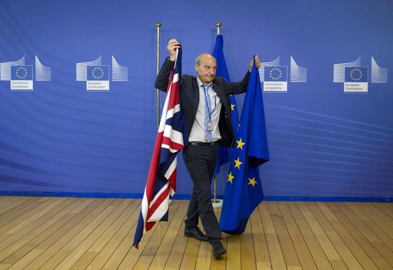 Служител на Екворейската комисия подменя флаговете на ЕС и Великобритания