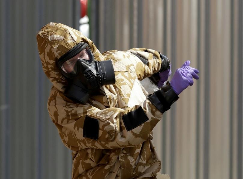 Британски служител на реда, облечен във военен защитен костюм