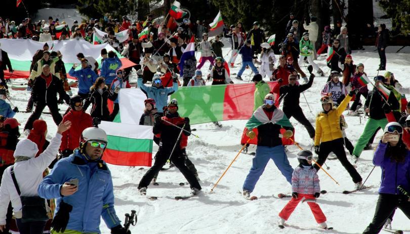 снимка 1 На ски с българското знаме и народни носии в Пампорово