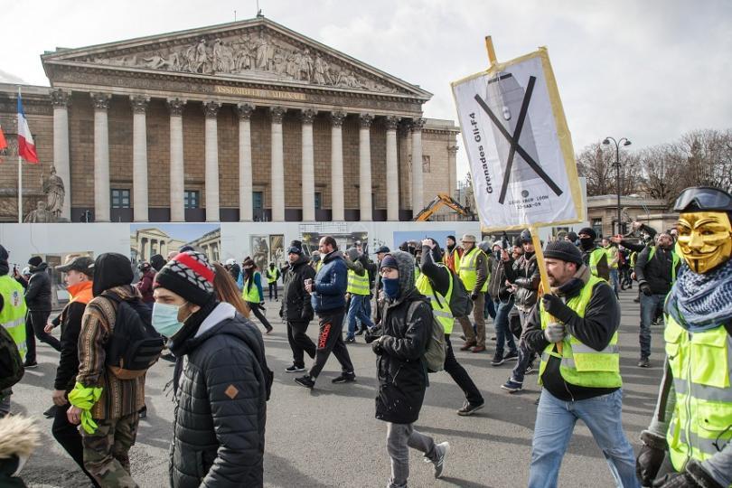 Демонстрант носи транспарант с надпис, призоваващ полицията да спре да употребява сълзотворни гранати